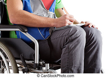 Disabled student writing the notes - Student on wheelchair...