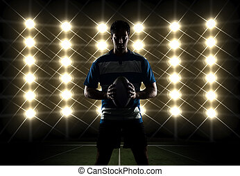 Rugby player silhouette in front of lights in a blue...