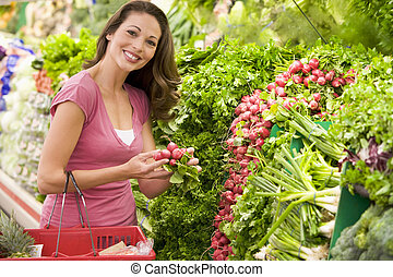 Woman shopping for beets at a grocery store