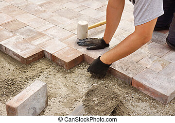 Worker installing paver - Man or trade worker installing...