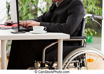 Lawyer on wheelchair working on laptop and driniking coffee