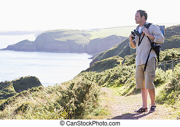Man standing on cliffside path
