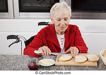 Disabled life - Disabled older woman preparing sandwiches...