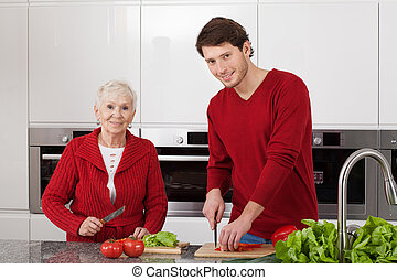Family cooking - Young man helping grandma to prepare a...