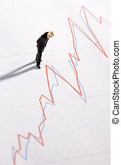 Figurine Of A Businessman Standing On A Line Graph