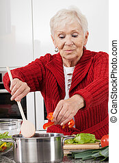 Grandma cooking - Active elder person preparing lunch for...