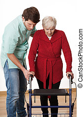 Walker lesson - Nurse teaching elder disabled person how to...