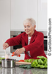 Grandma cooking - Happy active grandma is cooking lunch for...
