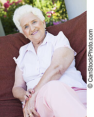 Senior woman sitting outdoors on a chair