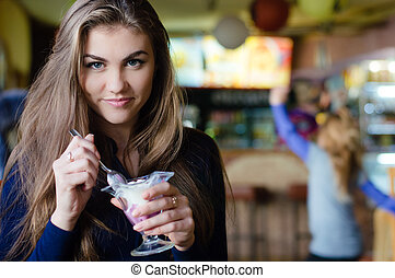 Young happy woman eating ice cream in cafe closeup portrait