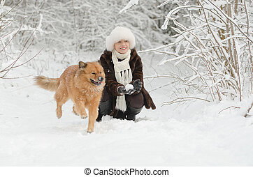 Young woman playing with dog in the