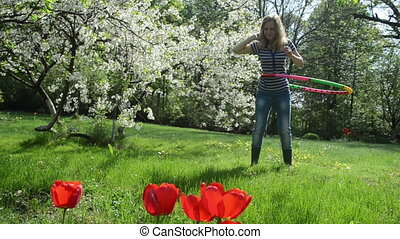woman spin hoop waist - pretty woman turn colorful hula hoop...