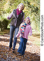 Grandmother and granddaughter walking on path outdoors...
