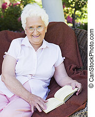 Senior woman sitting outdoors on a chair reading a book
