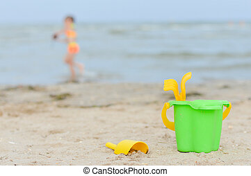 Little girl playng on sandy beach toys closer to viewer