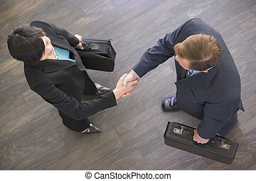 Two businesspeople indoors shaking hands