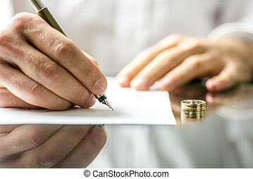 Signing divorce papers - Closeup of a man signing divorce...