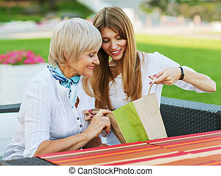 Adult mother and daughter drinking tea or coffee. They...