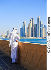 Arab man in national dress looks at the city of Dubai -...