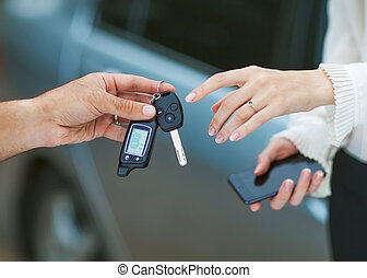 Male hand giving car key to female hand.