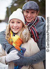 Couple in winterwear - Portrait of happy guy embracing his...