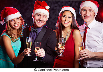 Christmas toast - Company of friends in Santa caps holding...