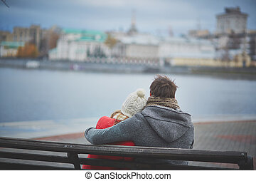 Togetherness - Back view of affectionate couple sitting on...
