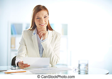 Friendly manager - Young businesswoman sitting at workplace...