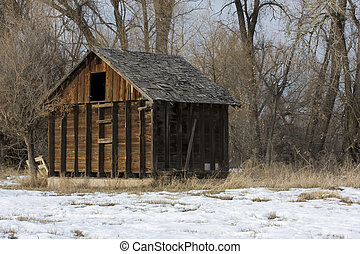 old, small barn in an abandoned farm in Colorado with a...