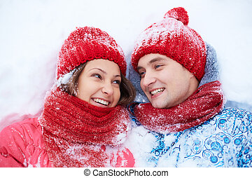 Dates on snow - Portrait of happy young couple lying on snow...
