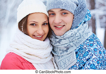 Couple in winterwear - Portrait of happy young woman and her...