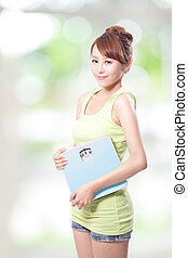 Happy woman holding a weight scale, asian