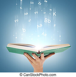 hand holding open book with magic lights - education and...