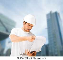 male architect in helmet looking at blueprint - building,...