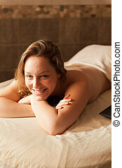 Beautiful woman in a spa relaxing on a massage table -...