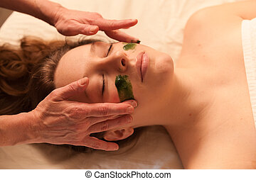 Beautiful woman receiving a facial massage in a spa -...
