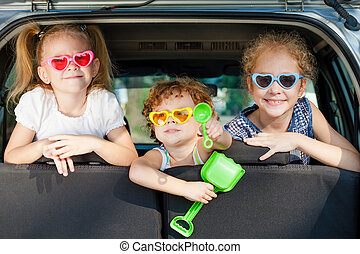two little girls and boy sitting in the car