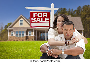 Hispanic Couple, New Home and For Sale Real Estate Sign -...
