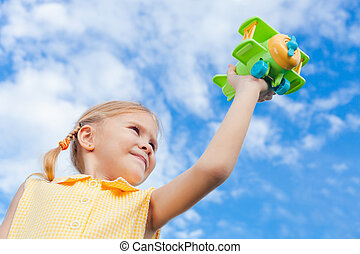 little girl with toy airplane in hands