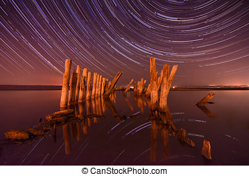 Pillars in the water at night on a background star trails