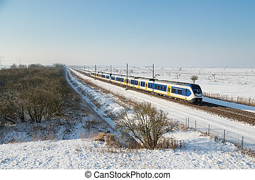 Yellow train in Dutch rural winter landscape of National...