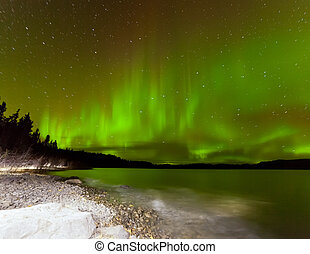 Aurora borealis night sky over Lake Laberge Yukon - Night...