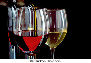 Red and white wine in bottles and wineglasses on black...