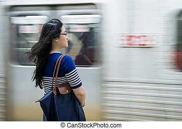 Young woman waiting at subway station with moving train