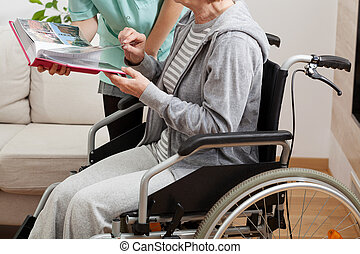 Caregiver - Good nurse viewing a photo album with her...