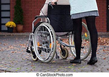Disabled with nurse - Nurse walking with elder disabled...