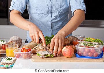 Healthy lunch preparing - A person cutting a sandwich while...