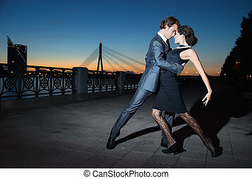 tango in the night city - young couple dancing tango on the...