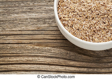 wheat bran - a ceramic bowl on grained wood background