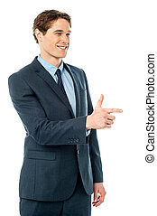 Cheerful businessman pointing away